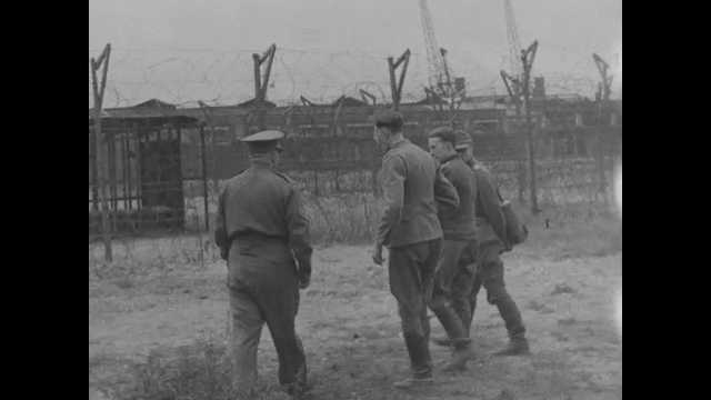 France 1940s: Allied officers talking inside prison camp. Officers walking. Nazi prisoner lying on ground. Soldiers giving rations to prisoners.