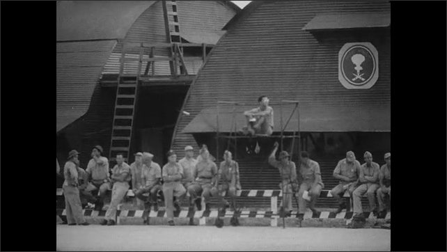 1940s Bikini Atoll: Soldiers stand and smile on airfield. Bomber plane dives through sky. Soldiers gather near hangers on airbase. B-29 Bomber lands on runway.