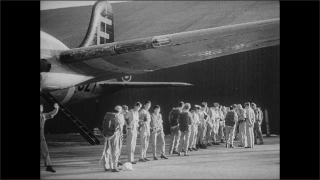 1940s Bikini Atoll: Soldiers stand and site on barricade and cars at air base. Bomber plane pilots and crew line up near plane at hangar.