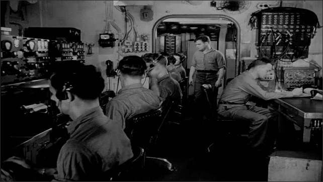 1940s: Aerial views of warships on water. Side view of ship on water. Crew working on ship. Man takes paper from typewriter, man takes paper to table. Man writes, man takes paper. Men at table.