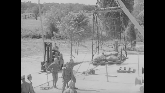 1940s: Soldiers by ropes, hand waving in foreground. Winch turning. Rope turning pulley. Crane lifting cargo, solders direct cargo to ground.