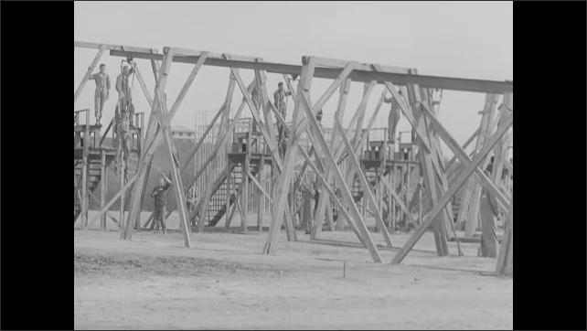 1940s: Tilt up, men climbing structure. Men walking up plank. Shots of men climbing down structure. Shots of men sliding down tracks, dropping to ground.