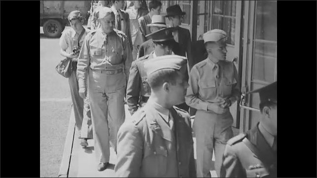 1940s: Officers exiting buses. Officers shake hands. Officers talking. Officers walk by building. Officers walk by shells in factory. Officers try on gas masks. Officers watching demonstration.