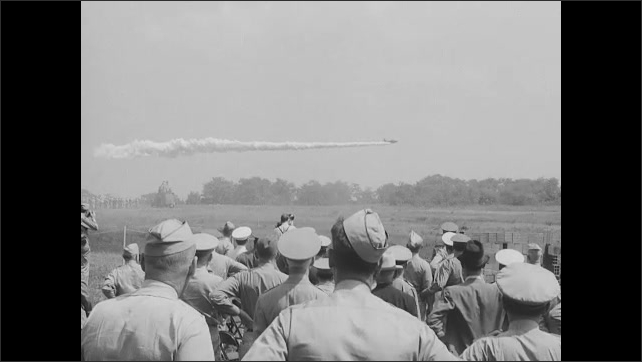 1940s: Officers sitting. Officer throws grenade. Explosion in field. Officers watching. Pan of plane flying, officer in foreground. Explosions in field. Rear view, officers watch explosions.