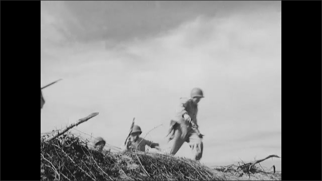 1940s: Soldiers crawl across ground, under barbed wire, in training exercise. Soldiers climb dirt hill.