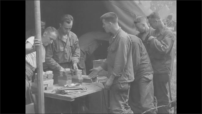 1940s: Soldiers in tanks drive down dirt road. Soldiers stand in line for supplies at camp. Soldier fits gas mask on face. Soldiers receive supplies and money.