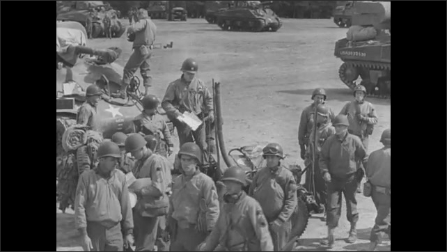 1940s: Group of soldiers sits on ground, listens to officers. Rows of vehicles parked behind soldiers. Soldiers prepare for departure from camp.