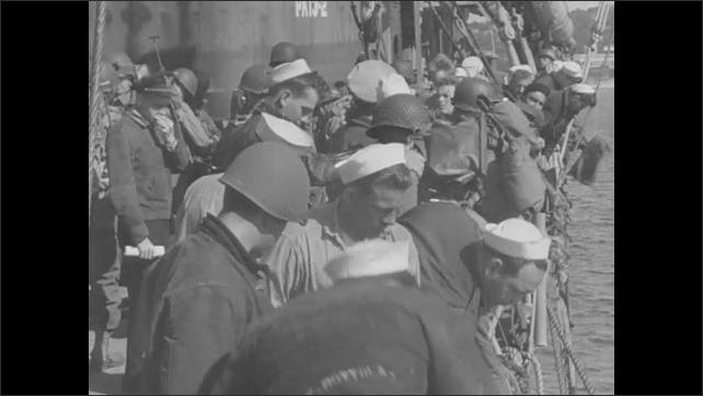 1940s: Men climb net to board ship. Ships wait in harbor.