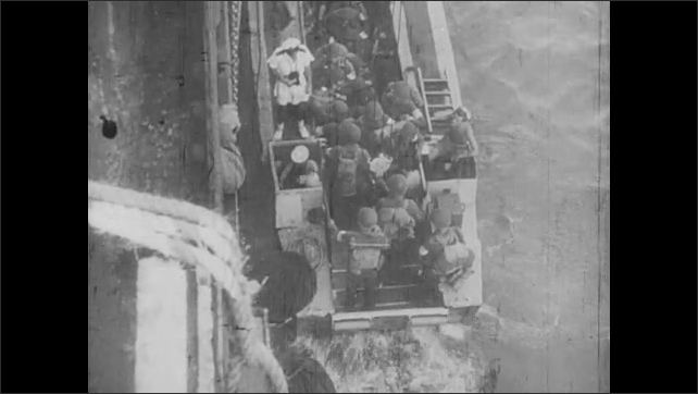 1940s: Officer on ship looks through binoculars. Guns on ship fire. Soldier climb down from boats into smaller boats. Soldiers on boats headed for shore as explosions in water around them occur.