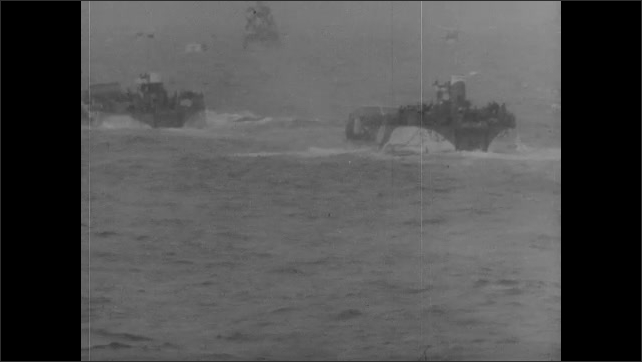 1940s: Soldiers pull other soldiers onto beach. Ships fire weapons. Soldiers stumble across beach by cliffs.