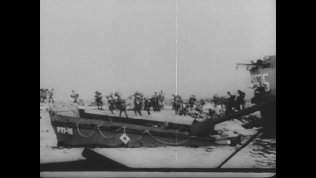 1940s: Soldiers exit ships onto beach. Tank drives past dead soldier.
