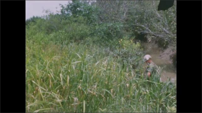 1960s: Soldiers walks down muddy embankment. Soldiers walk up grass embankment.