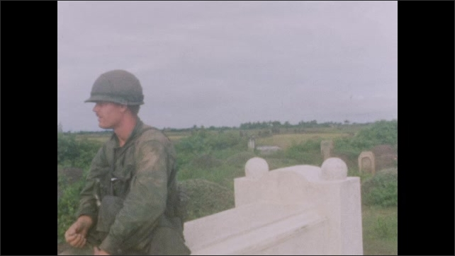 1960s: Soldier outside grass building. Soldiers sit on graves. Soldier walks by field.