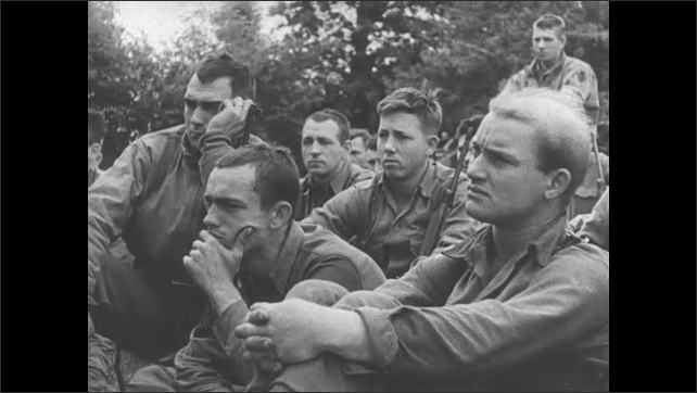 1940s: Soldiers and vehicle on ship.  Men watch airplane take off.  Men speak to group of soldiers.  Classroom.  Man smokes.  Men raise flag on ship.