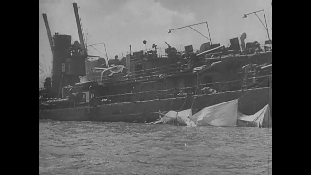 1940s: View of shore and destroyed buildings. Damaged ship. Man speaks at pulpit.