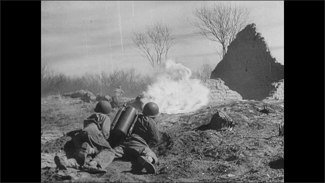1940s: Vehicle drives through smoke. Men on battlefield. Cannons fire. Explosions. Fighter jet gains altitude, then drops.