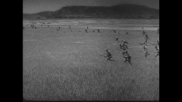 1940s China: Soldiers run across field. Map shows Chinese retreat from Japanese invasion. Chinese soldiers march down road. Japanese pilots stand together outside. Planes fly in formation.