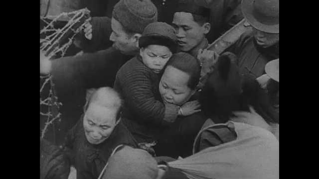 1940s China: Crowds of people push through streets. Buildings topple. Bombs explode. Planes drop bombs on city. Buildings burn. People walk through rubble of city.