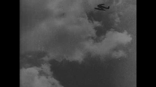 1940s China: Plane flies through the sky. Bombs land in water. Wounded soldiers board lifeboats. Boat speeds away. Ship sinks. Soldiers defend city. Soldiers overrun city.