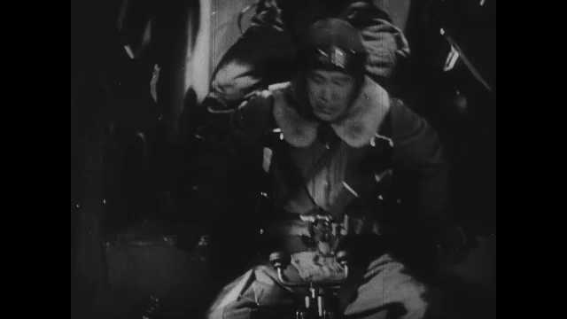 1940s: Gunners in bomber. Biplanes in sky. Dogfight in sky between fighter planes. Gunner on planes fires gun. Fighter is hit. Spinning in sky. Fightger plane in dogfight, shoots other plane.