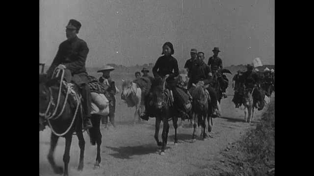 1940s: People ride on donkeys, mules down road. People stand in lines. Soldiers marching. Soldiers doing exercises in rows.