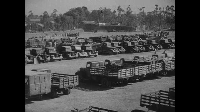 1940s: Rows of parked military trucks. Large oil silos. Cannons in factory. Airplanes on airstrip. Navy ship.