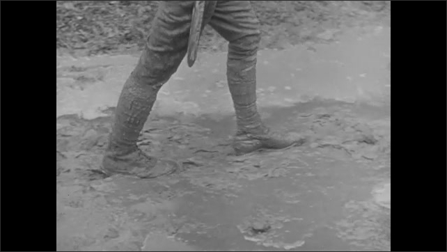 1940s: Soldier walks on cobblestone pavement. Revolutionary war soldier marches on cobblestone pavement. Soldier in WWI uniform walks in mud. Men walk down street. Soldiers walk through woods.