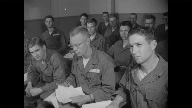 1940s: Soldiers sit at desks in classroom. Soldiers watch television at front of classroom. Satellite antenna sits beside house and sign.