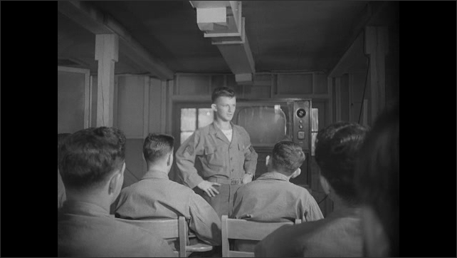 1940s: Soldiers sit in auditorium and receive live instruction. Soldier speaks to classroom. Soldiers watch television at front of classroom. Soldier passes papers to men at desks.