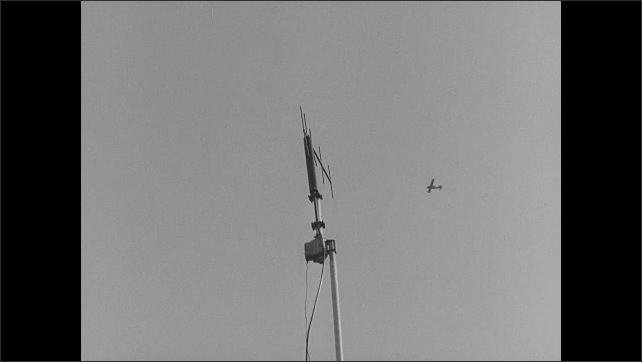 1950s: Airplane.  Man films from window.  Cockpit.  Antenna.  Trees.