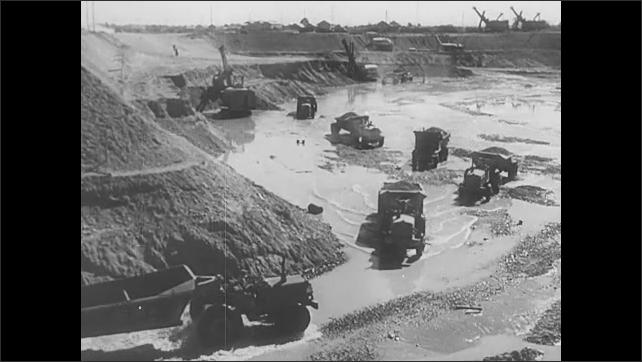 1950s Europe: Men exit bus. Men observe flock of sheep. Men gather and talk near construction site. Trucks drive through construction site. Men and machines build dam.