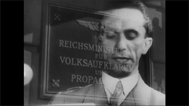 1940s: Newspaper headlines. Nazi plaque for Ministry of Propaganda. Radio. People in audience. Joseph Goebbels speaks. Nazi officers on panel. Men digging ditch.