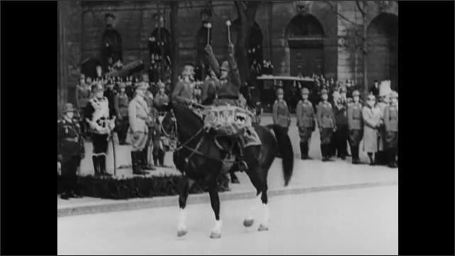1940s: Adolf Hitler smiles. Generals wave. Man rides horse, plays drum. Crowds cheer.