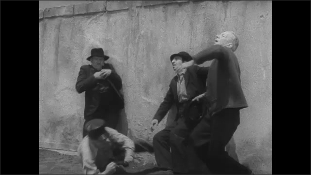 1940s EUROPE: Men giving Nazi salute. Woman accepts parcel from woman. People at work in field. Woman speaks. Men fall down. Himmler. Man chops with axe. Swastika. Men march in formation.