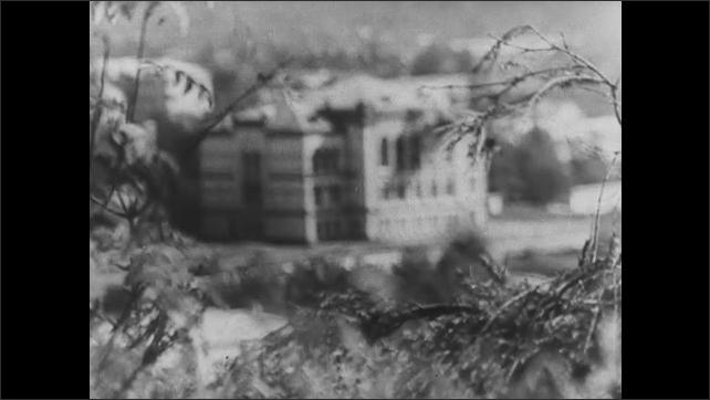 1940s EUROPE: Soldiers run, jump in ditch. Gun firing. Soldiers loading gun. Close up of soldiers. Gun firing. Chimney collapses. Guns firing. Adolph Hitler. Pan across destruction. Church interior.