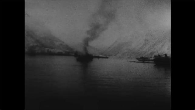1940s: Cannons on navy ships fire. Smoke rises from boat. Explosion on boat. Boats on fire. Soldiers on boats. Soldiers run across land.