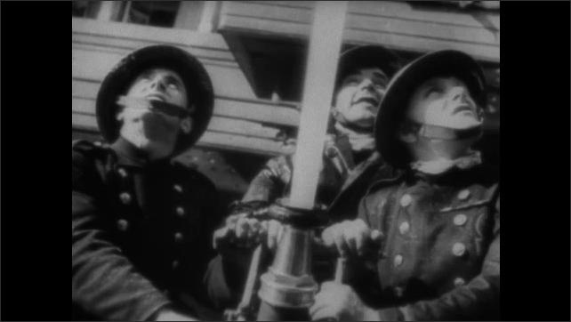 1940s ENGLAND: Men at work in rubble. Men speak. Men carry stretcher. Firemen spray water on fire. Men drink. Men and women speak. Women walk down street with officer.