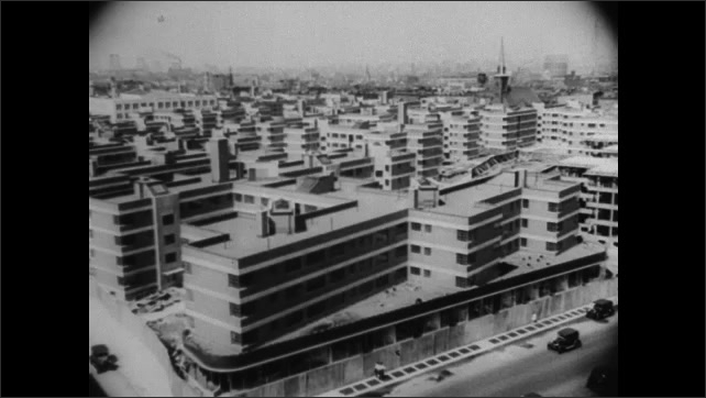 1940s: People walking. Crane lifts bucket. Aerial view of freeway interchange. Buildings in city. People on sidewalk, crossing street.