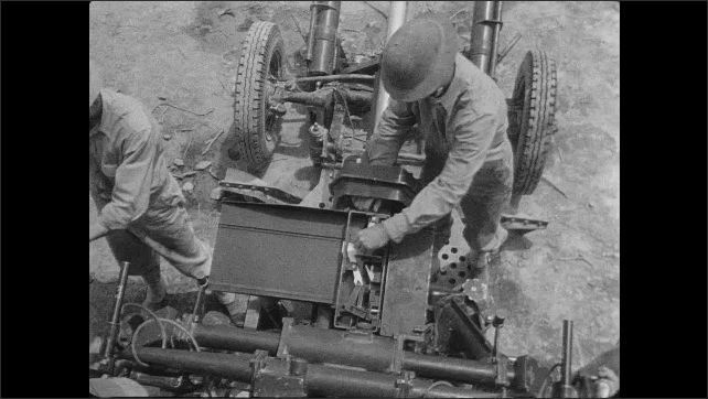 1940s: Soldier looks through scope on anti-aircraft gun. Platoon unload ammo from anti-aircraft gun. Commander inspects gun receiver and breach.