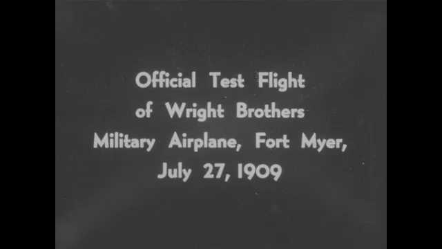 1900s: Intertitle card. Several people open hangar doors where airplane is.