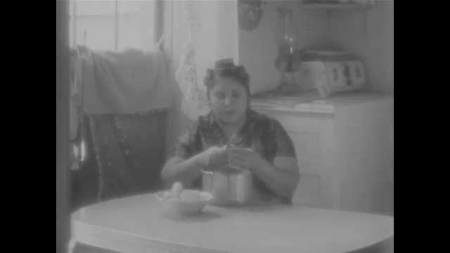 1960s: Woman talks while peeling potato at table in kitchen.