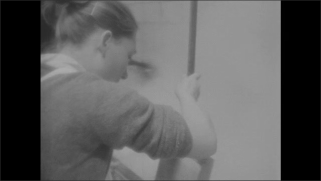 1960s: Man works with steaming liquid in factory. Woman stirs liquid in tub. Man checks temperature on thermometer in steaming liquid.