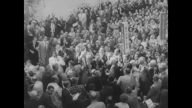 1960s: Crowd in political convention with signs, crowd cheering. Crowd cheering. John F Kennedy walking from stage. Women in costume applauding.