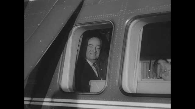 1960s: Hubert Humphrey waves from window of helicopter.  Crowded convention hall.  Large photo of Lyndon Johnson. Women stand on platform.  Men wave signs.