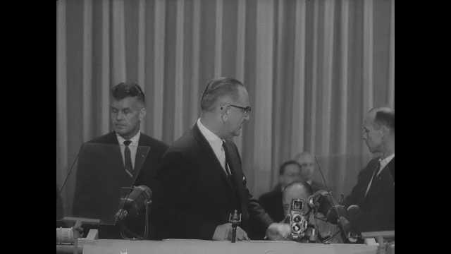 1960s: Lyndon Johnson speaks on stage.  Men stand.