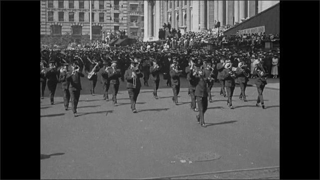 1910s: Float in parade. Marching band. Men in top hats. Floats in parade.