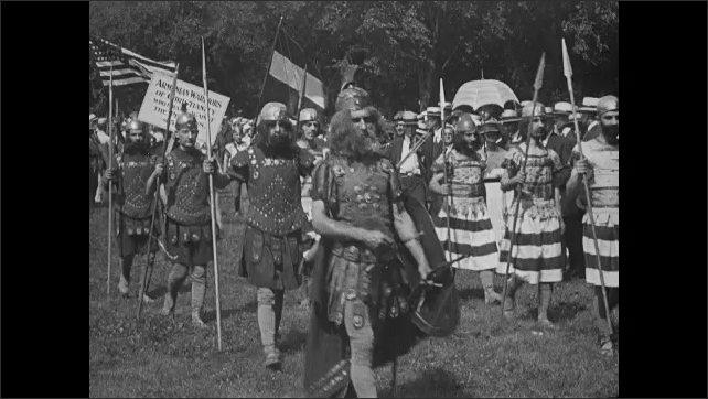 1910s: People walk carrying sings, across grass, some dressed as Roman soldiers.