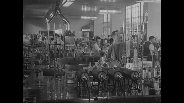 1930s: Cog, wheel in factory. Person operates machinery. People at work in industrial lab.