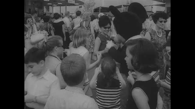 1960s: Children at park, in stroller. Monorail. Officer escorts child into building. Officers talk to child. Children sit at table and color. Woman escorts child and adult out of building.