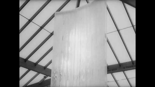1960s: Tilt down fountain. Tracking shot of machinery. Pan of shapes. Reflection, lights flashing. Tracking shot, train enters building. Amusement park ride. Train driving. Tracking shot of building.